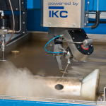 Detail of a waterjet rotating on an axis to cut tube