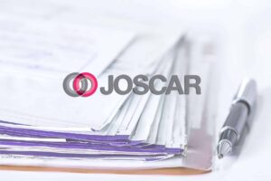 Image of the Joscar logo with paperwork in the background