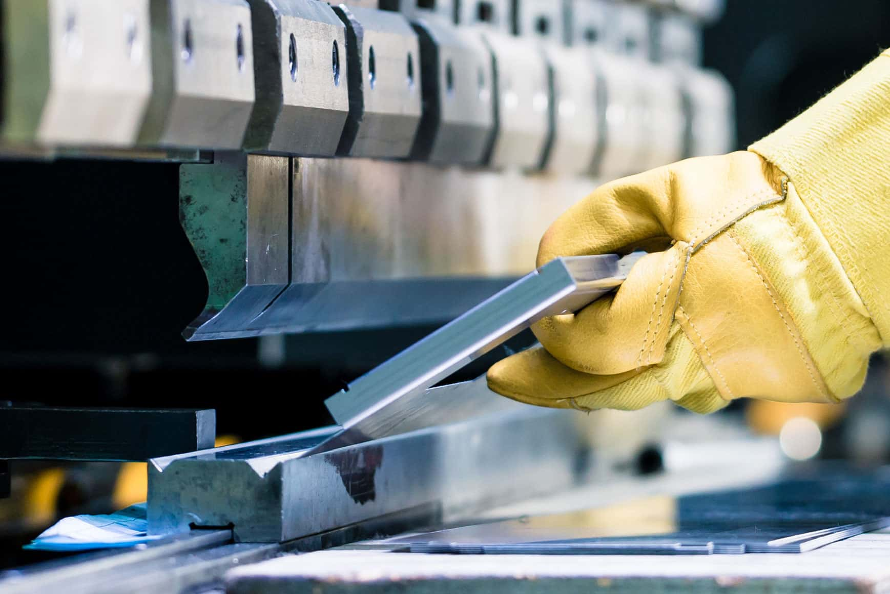 Image of gloved hands holding a piece of metal on a pressbrake