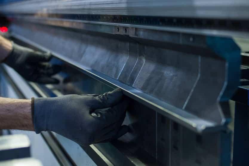 Image of hands adjusting top tooling on a pressbrake