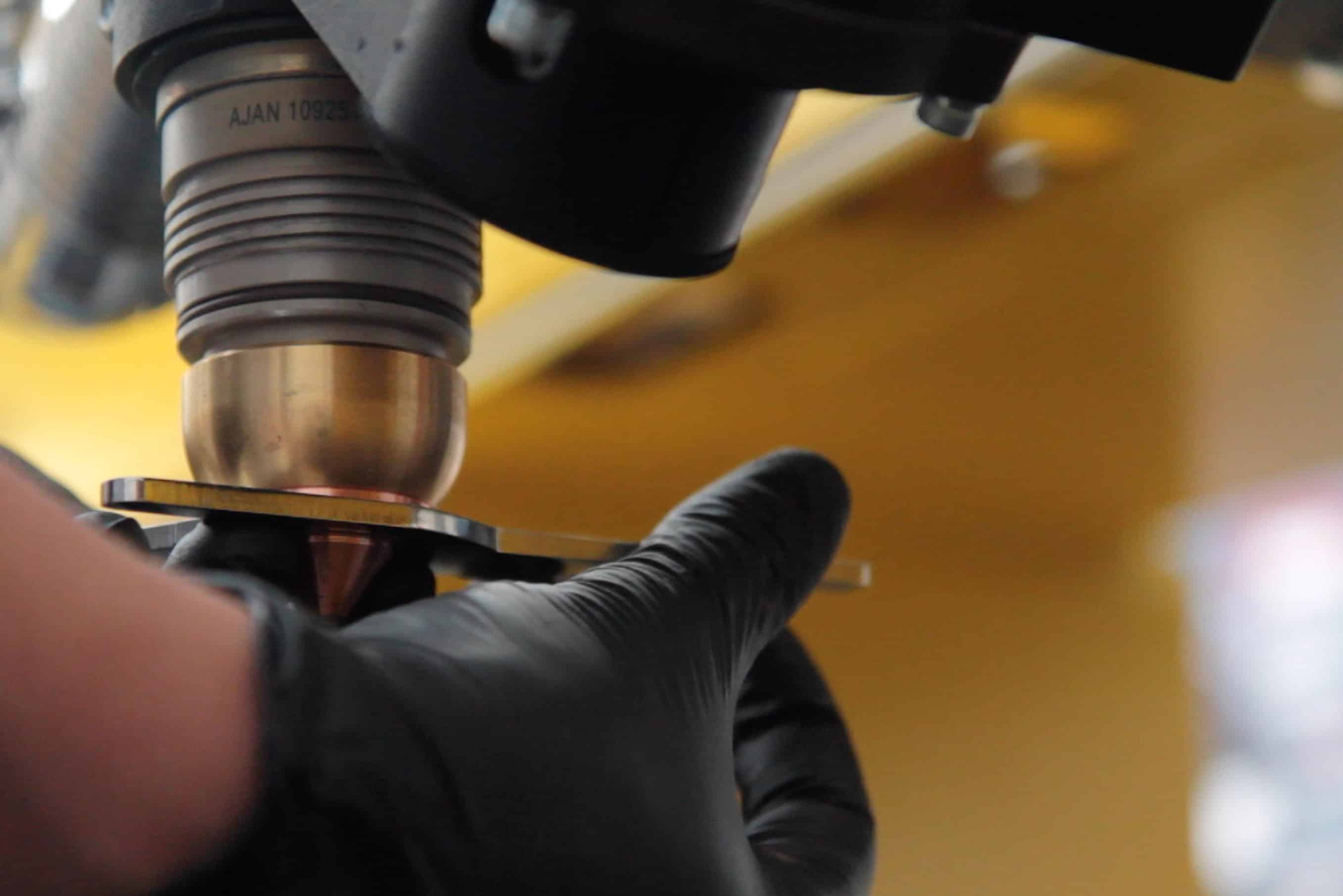 Close up image of a hand removing the Shield Cap on the Ajan Plasma Torch