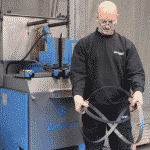 A technician demonstrating how to uncoil a bandsaw blade safely