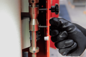 Close up of a hand adjusting the stroke limit switches on a steelworker