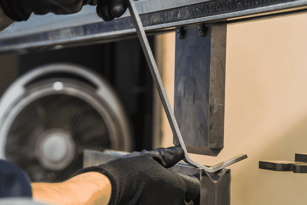 Close up of hands putting a piece of metal up to press brake tooling to fold