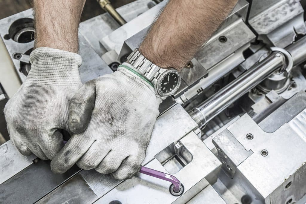 Image of hands fixing a machine