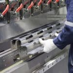 Image of gloved hands working at a pressbrake