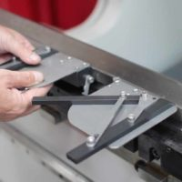 Image of hands attaching the squaring arm onto a press brake