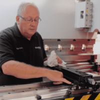 Image of a Selmach engineer inside the press brake conducting general maintenance on the backgauge