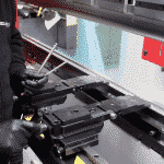 View of operator adjusting a press brake backgauge inside of the machine