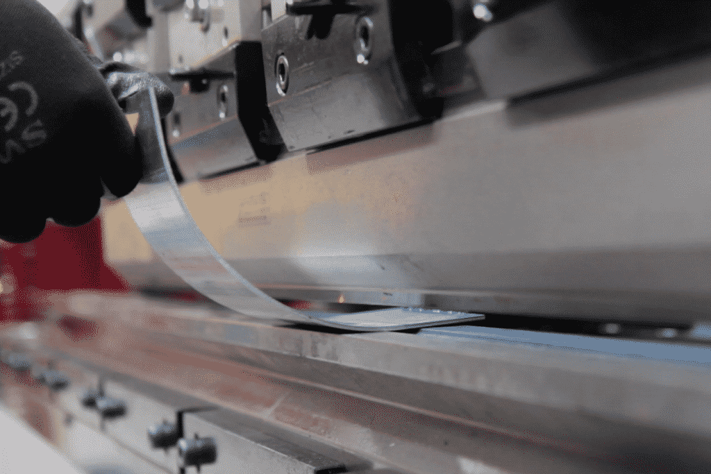 A piece of metal being curved via bump bending on a press brake