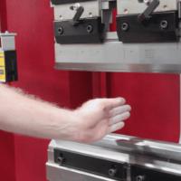 Operator demonstrating the laser light guard on the front of Morgan Rushworth Press Brake