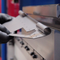Close up metal being curled on a press brake