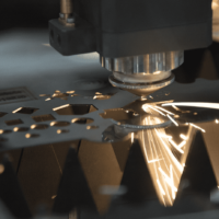 Close up of Laser Cutting head cutting intricate sections on a metal sheet
