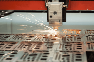 Close up image of the cutting head cutting metal on a Fibre Laser